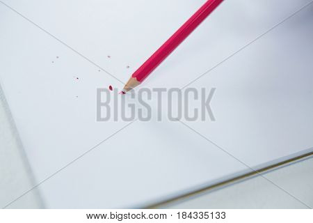 Red colored pencil with broken tip with notebook on white background