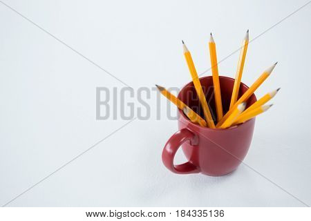 Close-up of yellow color pencils kept in mug on white background