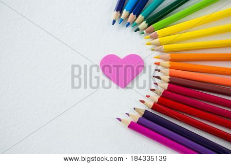 Close-up of colored pencils arranged in semi circle with heart on white background