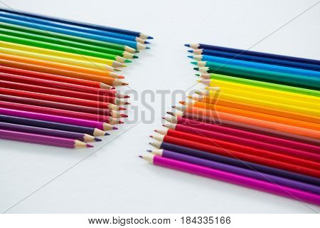 Colored pencils arranged in a row on white background