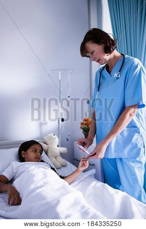 Female doctor checking a sugar level of patient in hospital