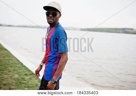 Stylish African American Boy Wear At Cap, Football T-shirt And Sunglasses. Black Sports Man Portrait