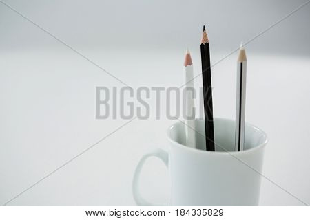 Close-up of black and white colored pencils kept in mug on white background