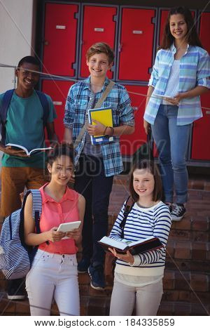 Portrait of students standing on staircase at school