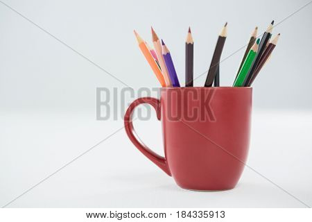 Colored pencils kept in mug on white background