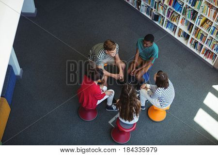 Overhead view of students interacting with each other in library at school