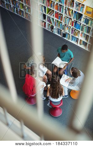 Overhead view of attentive students studying in library at school