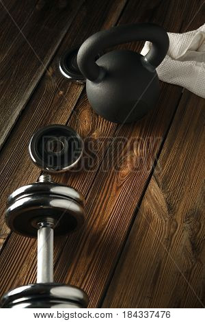 Top View Of Black Iron Kettlebell, Dumbbell And White Towel On Wooden Floor Sport Background With Co