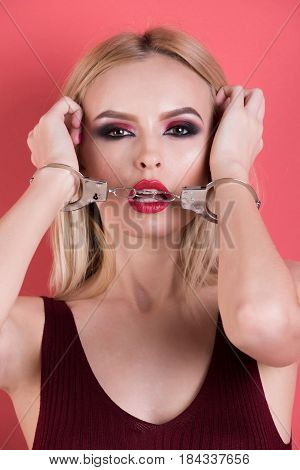 handcuffs on young woman or sexy girl with fashion makeup and blonde hair
