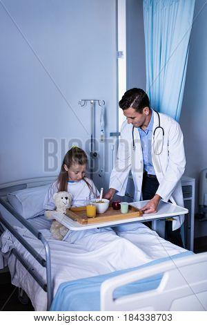 Doctor serving breakfast to girl in hospital