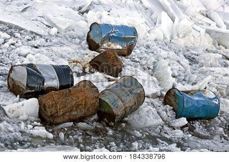 Metal rusted and damaged barrels in the frozen river. Environmental pollution and natural disasters.