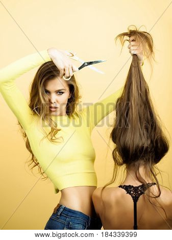 Beautiful Hairdresser With Scissors Cutting Long Hair To Blond Girl