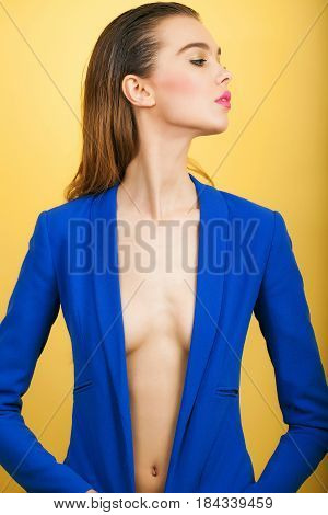 Sexy fashionable model or cute girl and pretty woman with stylish makeup long hair hairstyle in open blue coat with sexi breast and belly posing on orange background. Female fashion and beauty