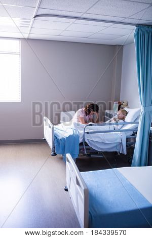 Sad doctor sitting with patient in hospital