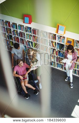 Students interacting with each other in library at school
