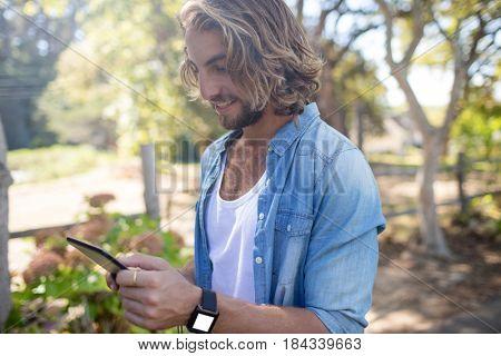 Happy man standing in park using digital tablet
