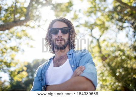 Confident man standing in park with arms crossed