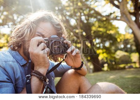 Man taking picture with digital camera in park