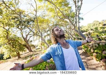 Happy man standing in park with arms outstretched