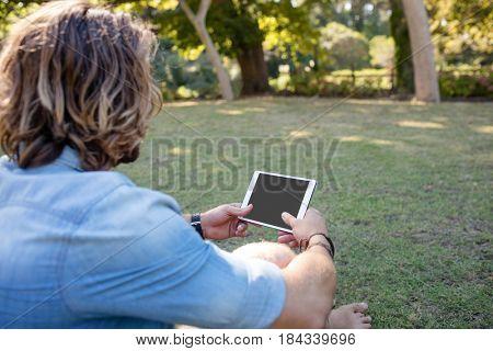 Man sitting on grass using digital tablet in park