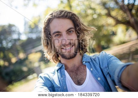 Portrait of smiling man standing in park