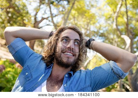 Happy man standing with hands behind head in park