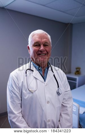 Portrait of smiling male doctor standing in ward at hospital
