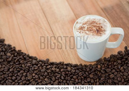 Coffee mug with roasted coffee beans on wooden background