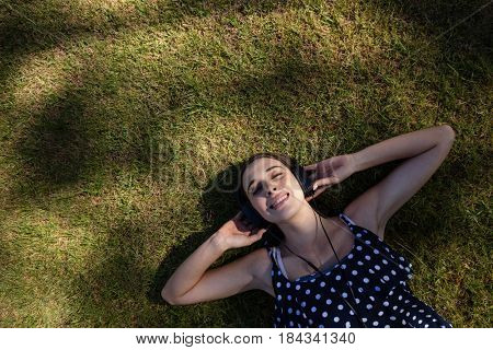 Woman lying on grass and listening to music with headphones in park