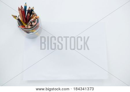 Colored pencils kept in pencils holder kept on blank paper on white background