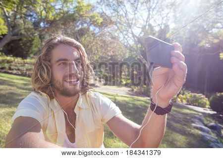 Happy man listening to music on mobile phone in park