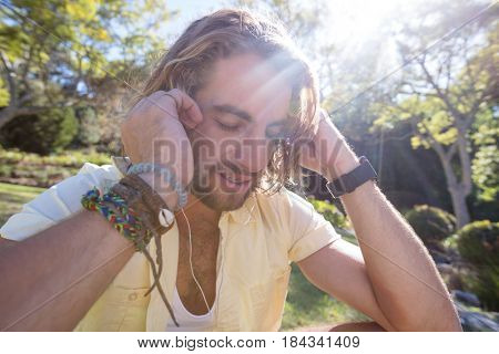 Close-up of man listening to music with earphone in park