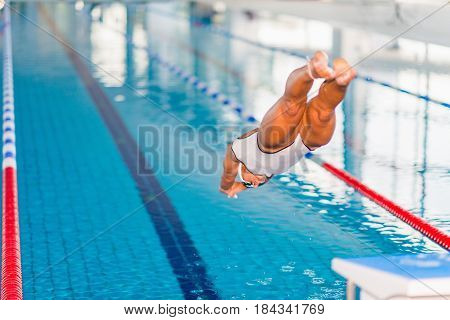 Female Swimmer Jumping In To The Poolfemale Swimmer Jumping In To The Pool, Color Image, Indoors