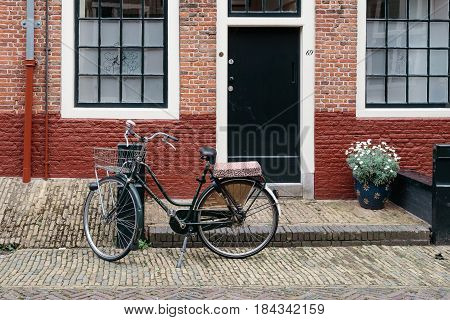 Haarlem Netherlands - August 3 2016: Beautiful traditional house in Haarlem with red brick and a bicycle parked in the front.