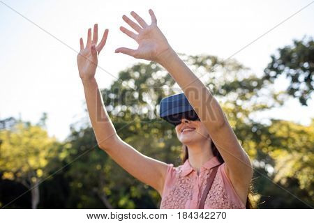 Smiling woman raising her hands while using a VR headset in the park on a sunny day
