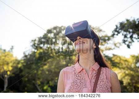 Smiling woman using a VR headset in the park on a sunny day