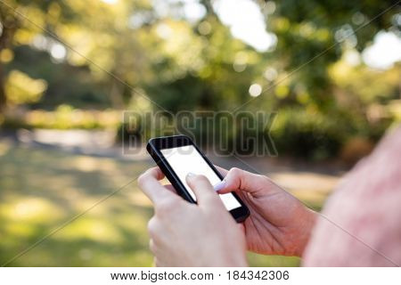 Close-up of womans hand using a mobile phone in the park