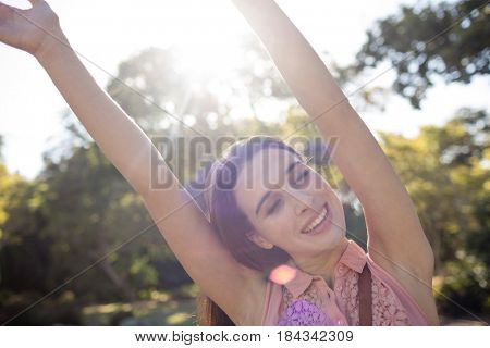 Portrait of happy woman standing in the park with her hands raised