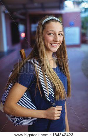 Portrait of happy schoolgirl standing with schoolbag in school campus