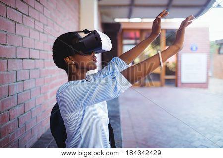 Schoolgirl using virtual reality headset in school campus