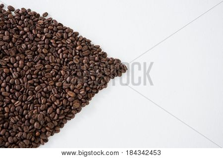 Coffee beans forming shape on white background