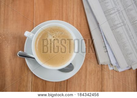 Coffee and newspaper on wooden background