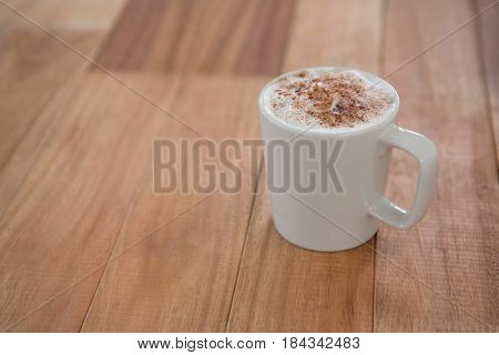 Coffee served in white mug on wooden table
