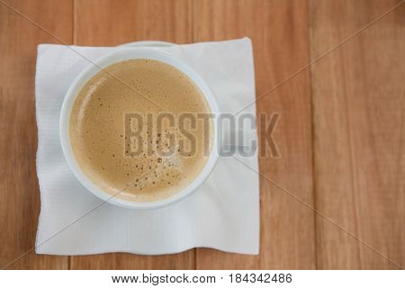 Coffee served with tissue paper on wooden table