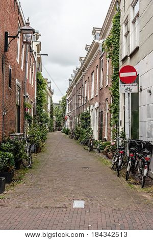 Haarlem Netherlands - August 3 2016: Picturesque cityscape of Haarlem near the cathedral with bicycles parked in empty green small street