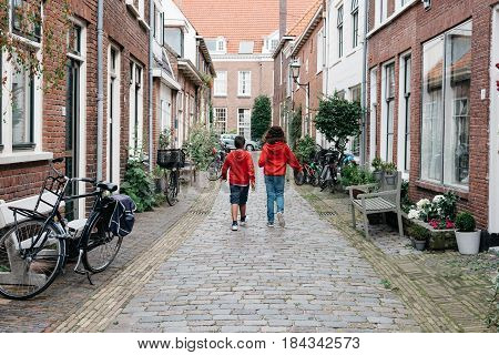 Haarlem Netherlands - August 3 2016: Kids walking in a picturesque street with beautiful traditional houses in Haarlem