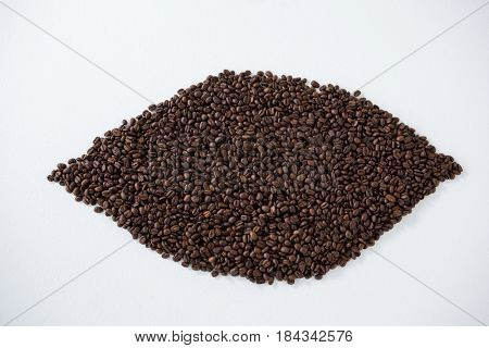 Coffee beans forming eye shape on white background