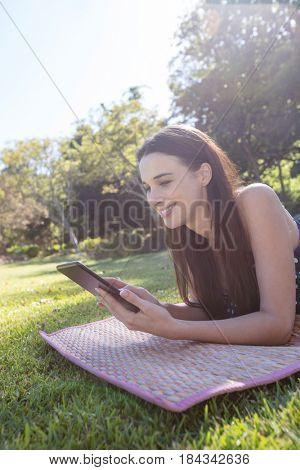 Smiling woman lying on mat and using digital tablet in park