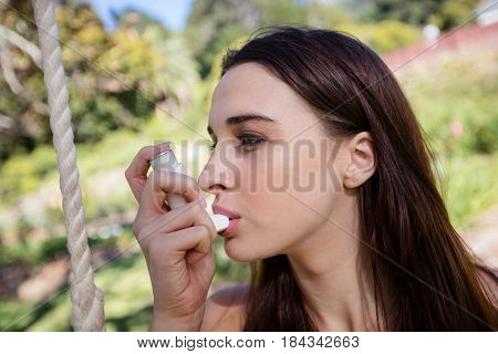 Woman sitting on swing using an asthma inhaler in park
