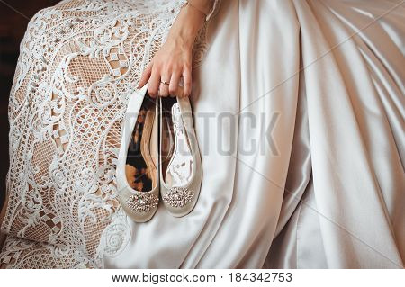 Bride holds the wedding shoes in her hands.
